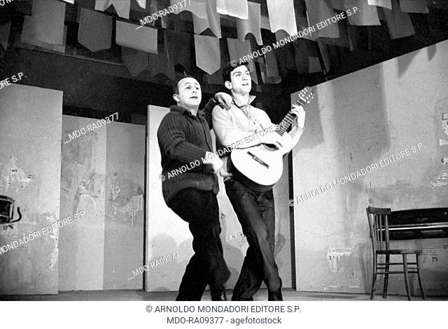 Italian actor Gigi Proietti, playing a guitar, and Italian actor and director Giancarlo Cobelli in the theater play Can Can degli italiani in Arlecchino theater
