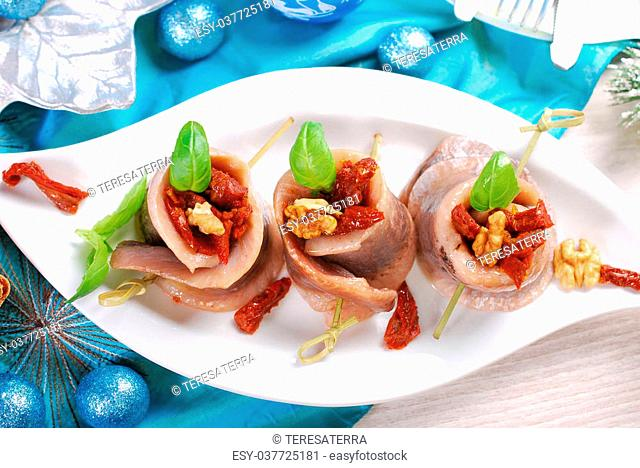 appetizer of spicy herring rolls with dried tomato and walnuts on christmas table