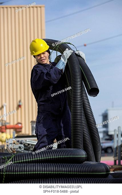 Female power engineer moving flexible drainpipes