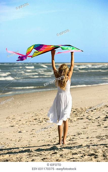 Caucasian pre-teen girl holding kite on beach