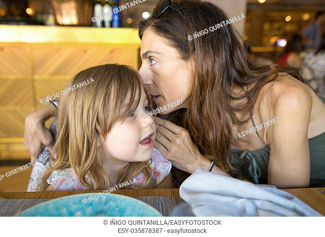 woman mother talking to ear to three years old blonde girl sitting in restaurant