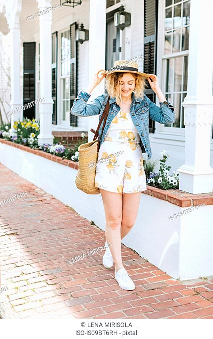 Young woman strolling on sidewalk wearing straw boater, Menemsha, Martha's Vineyard, Massachusetts, USA