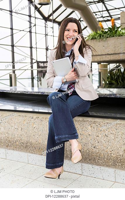 Mature business woman talking on her cell phone and holding a tablet in the atrium of an office building; Edmonton, Alberta, Canada