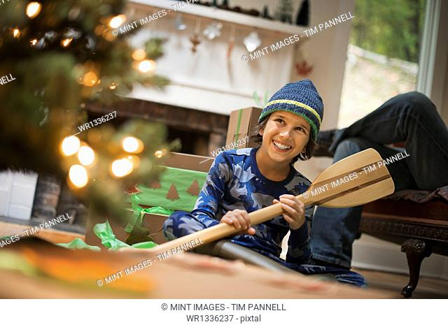 A boy by a Christmas tree unwrapping a gift, a wooden oar