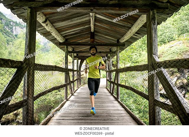 Italy, Alagna, man running on wooden bridge in the mountains
