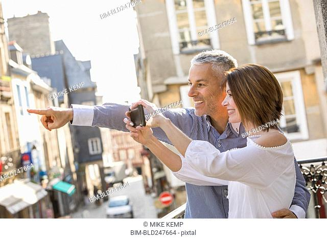 Caucasian couple photographing with cell phone in city