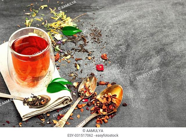 Still life, food and drink concept. Various kinds of tea with a glass of tea on a black chalkboard. Selective focus, copy space background