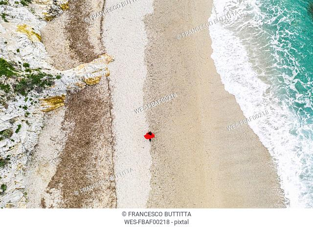 Italy, Elba, woman with red coat walking at beach, aerial view with drone