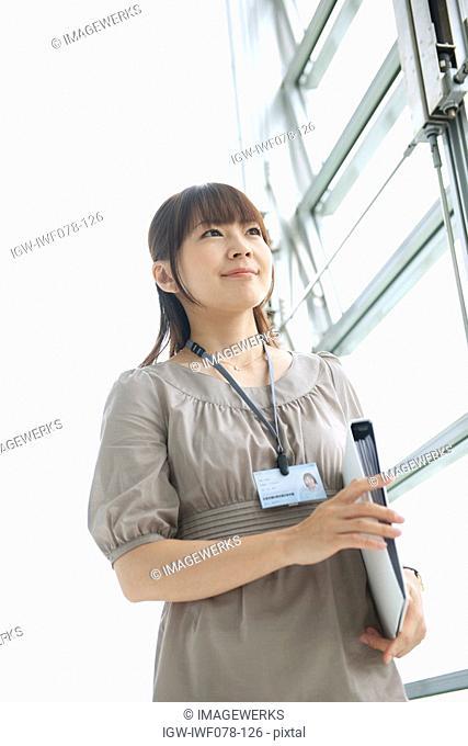 Japan, Osaka Prefecture, Businesswoman holding file, smiling