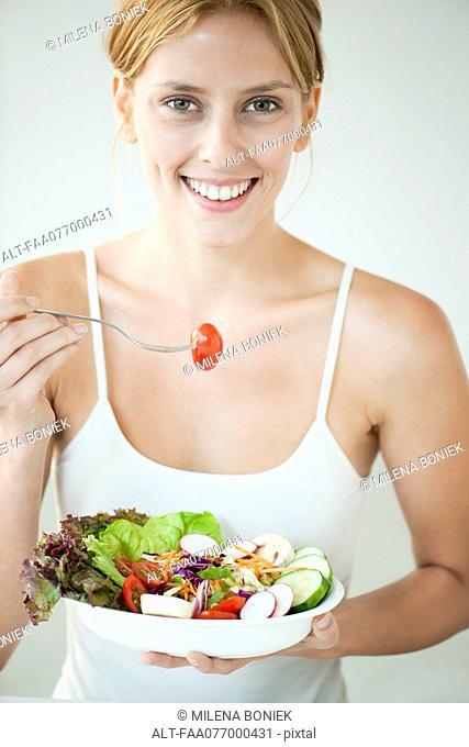 Young woman eating bowl of salad