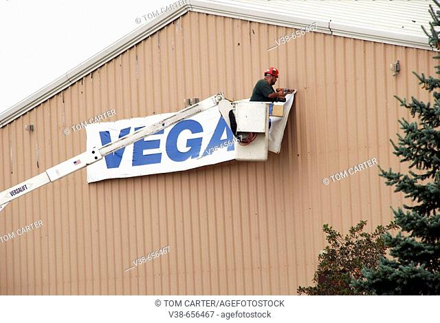 Workers remove a sign from the side of a building