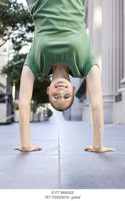 Businesswoman doing handstand on urban sidewalk
