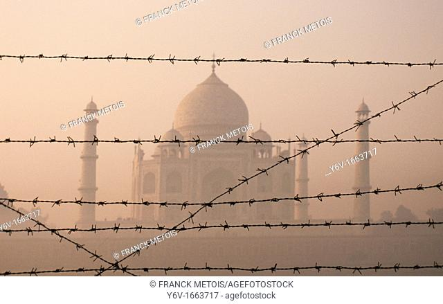 Taj mahal on a misty morning  The monument is seen behind barbed wires  Agra, India