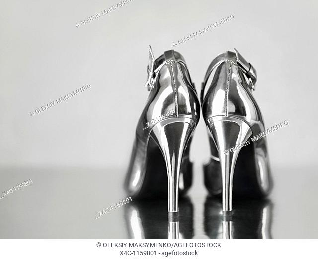 Stylish shiny silver stiletto high heel shoes staning on metal surface
