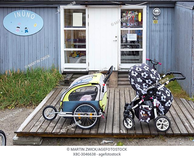 Pram in front of a kindergarten. Town Ilulissat at the shore of Disko Bay in West Greenland, center for tourism, administration and economy