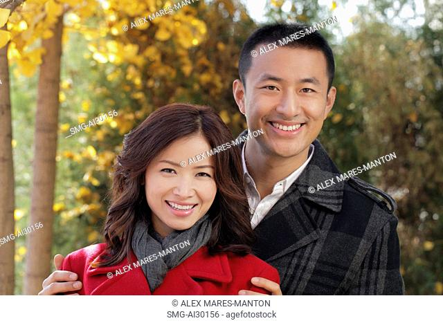 Young couple standing together under the trees