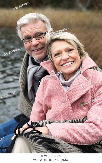 Germany, Kratzeburg, Senior couple sitting on boardwalk, smiling, portrait