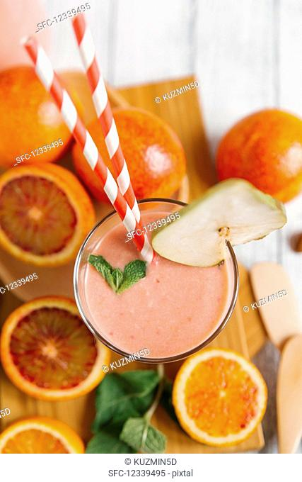 A blood orange smoothie with a straw in a glass (top view)