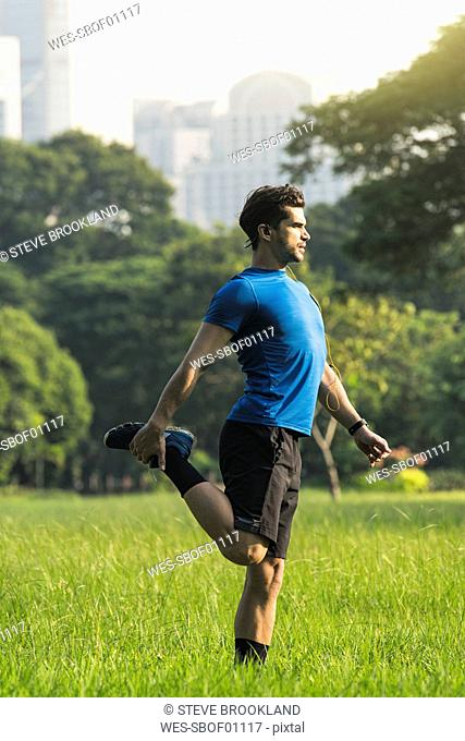 Runner warming up in urban park