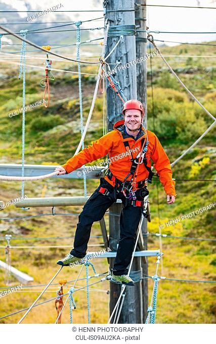 Man balancing at high rope access course, Iceland