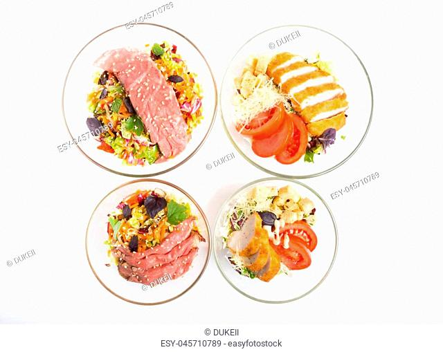 Salad with roast beef and chicken meat in a glass bowls