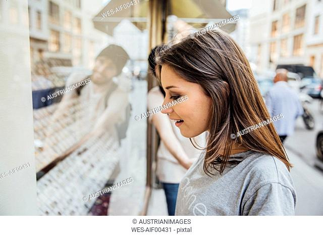 Young woman looking fascinated in shop window, boyfriend trying to pull her away