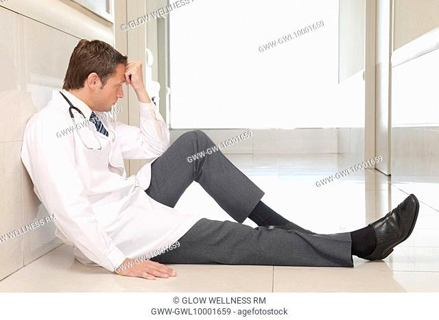 Doctor sitting on the floor looking depressed