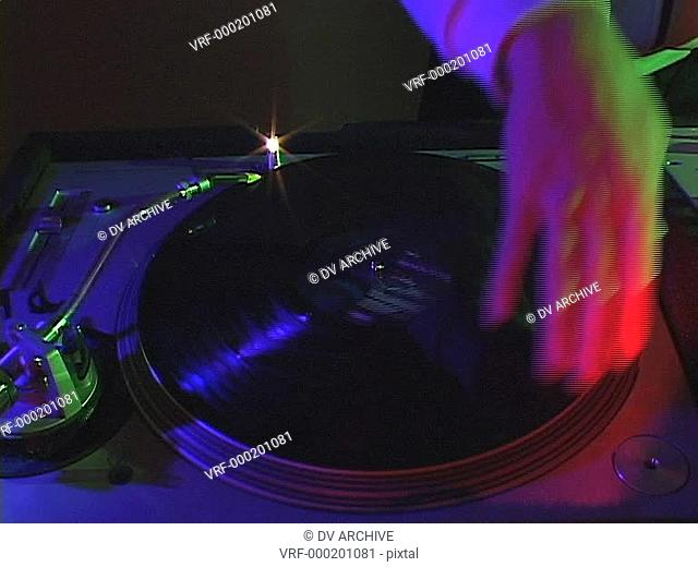 A DJ plays scratch music on a turntable