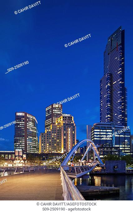 Melbourne Southbank skyline, Eureka Tower, the 2nd tallest building in Australia and Ponyfish Island Bridge over the Yarra River at twilight