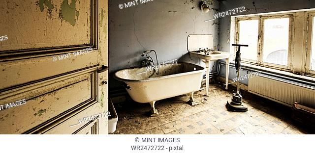 Interior view of abandoned bathroom, ball and claw tub and sink
