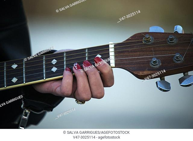 A woman's fingers on the strings on the mast of a guitar
