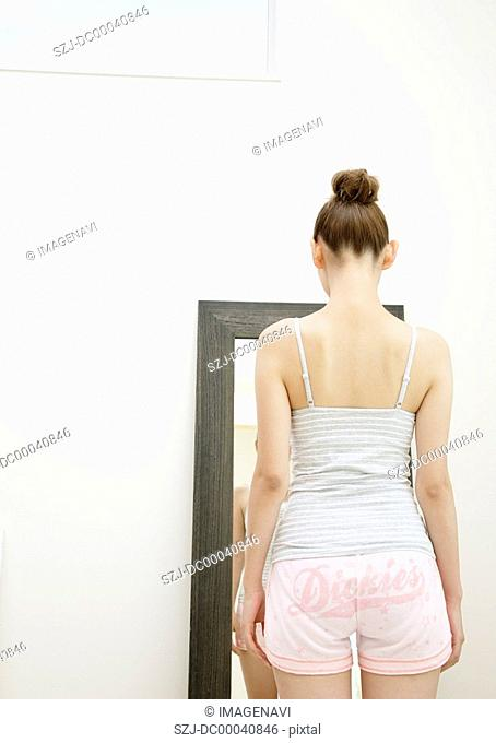 A young woman standing in front of a mirror