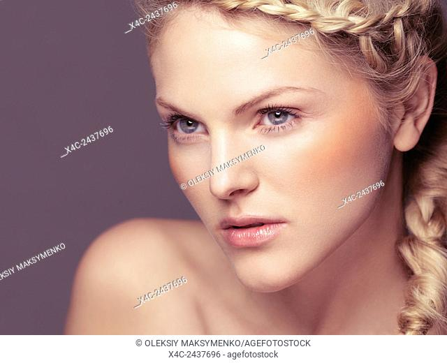 Beauty portrait of young woman with blond braided hair and glowing healthy skin