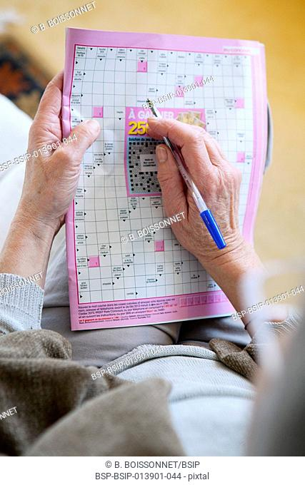 Elderly person doing cr-word puzzle