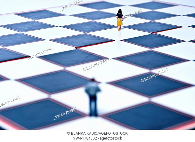 Toy man following toy woman or toy woman walking away from toy man