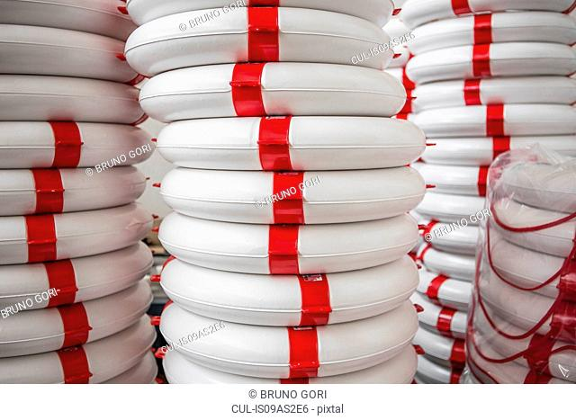 Stack of life buoys in factory that produces products for boating and camping