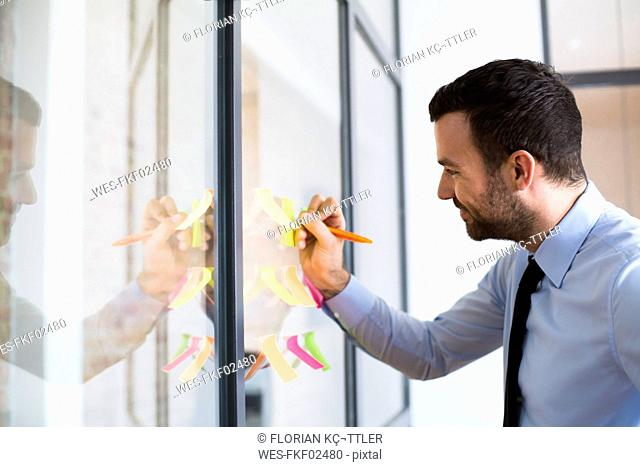 Businessman in office writing on adhesive note on glass wall