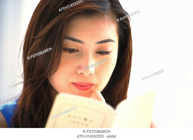 Closed Up Image of a Young Adult Woman Reading a Book, Low Angle View, Differential Focus