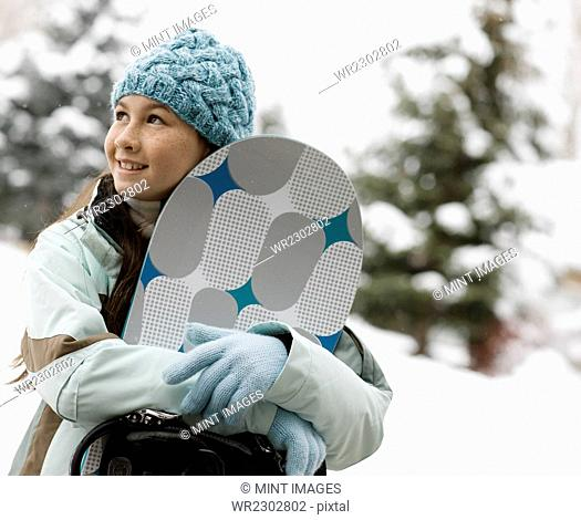 Winter snow. A girl in hat and gloves carrying a snowboard