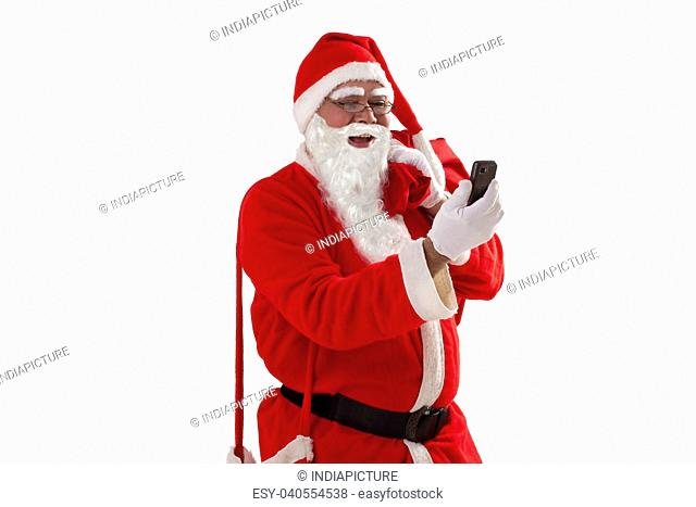 Front view of Santa Claus looking at mobile phone while carrying sack of Christmas presents