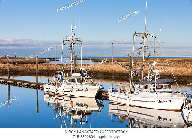Commercial fishing boats docked in a narrow tidal inlet called Scotch Pond near Steveston British Columbia