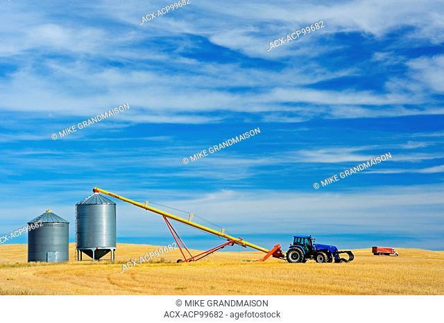 Grain bins, tractor and auger near Beechy Saskatchewan Canada