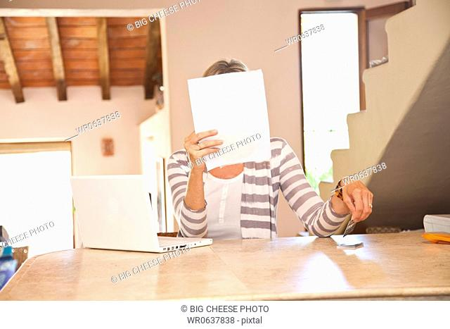 Woman in home office holding bills