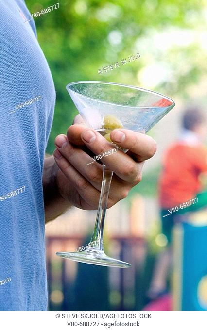 An empty stemmed martini glass held by thirsty host age 38, St Paul, Minnesota, USA