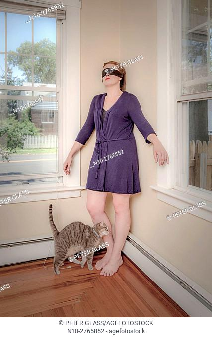 Young blindfolded woman and her cat in the living room