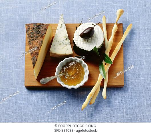 Still life with cheese, jam, olive and grissini