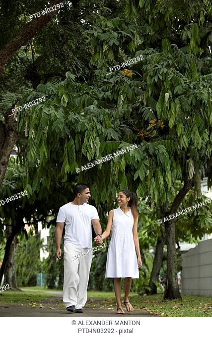 Singapore, Young couple walking along garden path holding hands