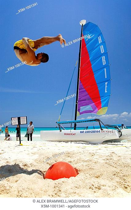 Man doing a somersault on Playa del Carmen Beach in the Mexican Caribbean