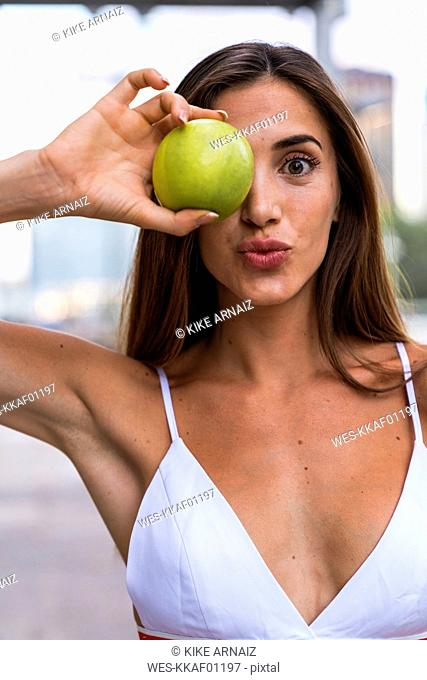 Portrait of attractive young woman wearing sports bra holding an apple
