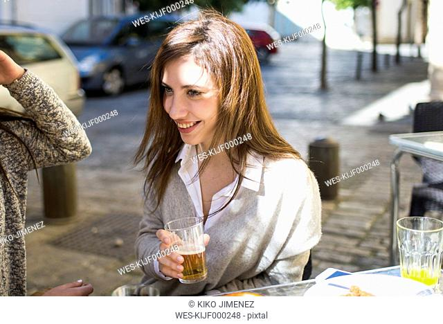 Portrait of young woman drinking beer in a street cafe